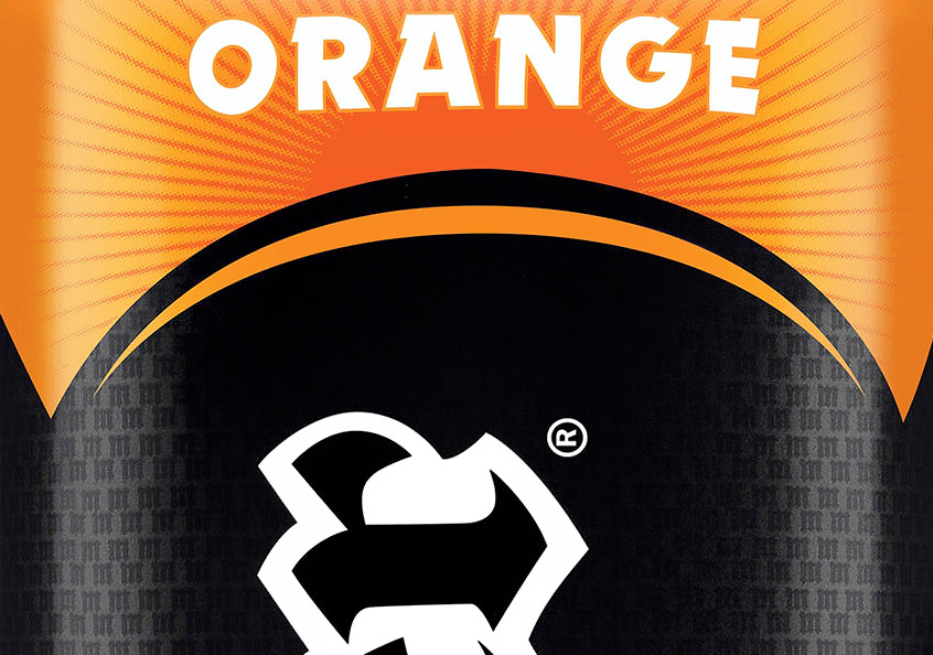 "Old can detail, showing the flavour name in Dynamo, and a pattern of ""M""s behind the logo"